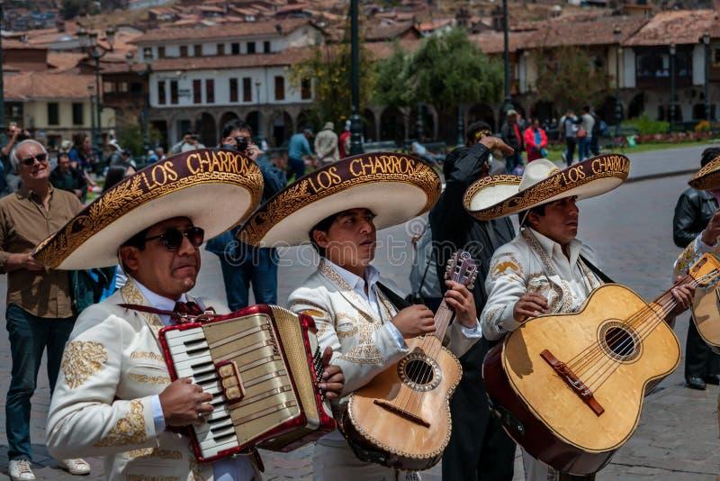 CUSCO, PERU - 7 DE OUTUBRO DE 2016: Os músicos latinos no sombreiro jogam guitarra e acordeão em um casamento foto de stock royalty free