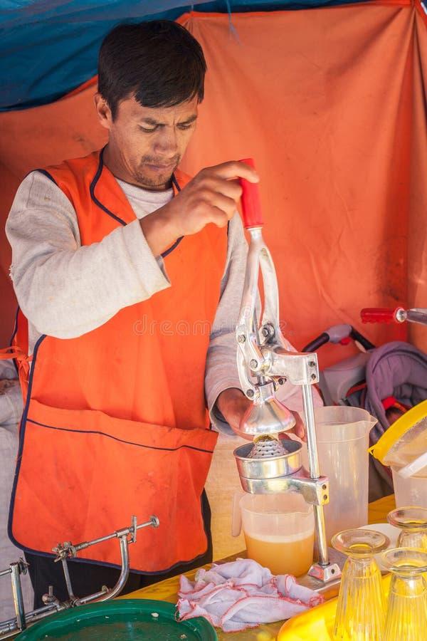 Cusco/Peru - Maj 27 2008: Latinsk manfruktsafttillverkare som pressar apelsiner royaltyfri bild