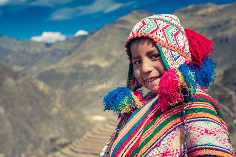 Cusco/Peru - Maj 29 2008: Stående av en pojke som ler uppklädd i färgrik infödd peruansk dräkt royaltyfri foto