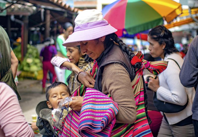 Peruvian indigenous mother carries her child while she feeds him. royalty free stock image