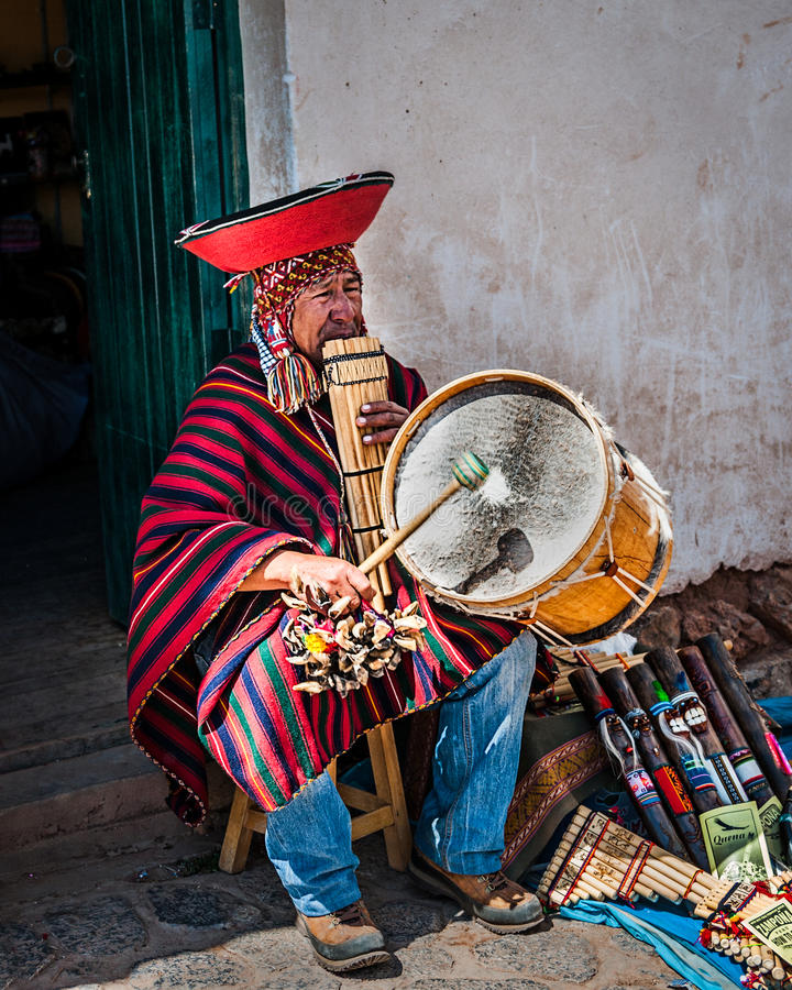 CUSCO, PERU - OCTOBER 1, 2016: native Peruvian playing national musical instrument Zampona Marimacha, dressed in colorful tradit royalty free stock photos