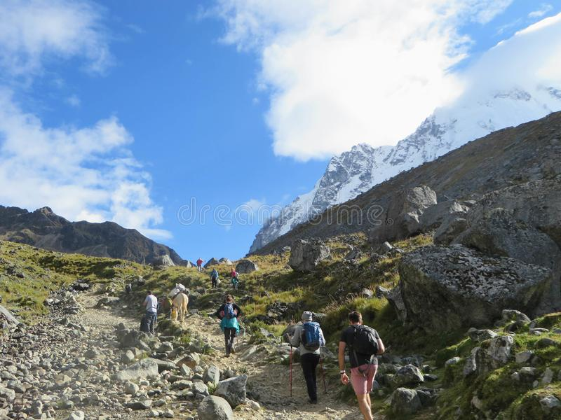 Cusco Province, Peru - May 8th, 2016: A young group of international hikers, led by their local Inca guide, navigate the Andes mo stock photography
