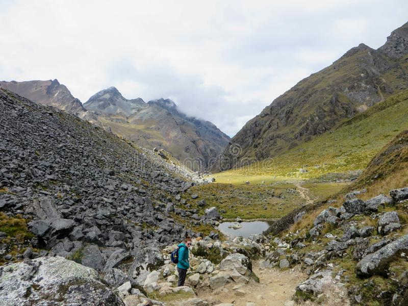 Cusco Province, Peru - May 8th, 2016: A young group of international hikers, led by their local Inca guide, navigate the Andes mo stock images