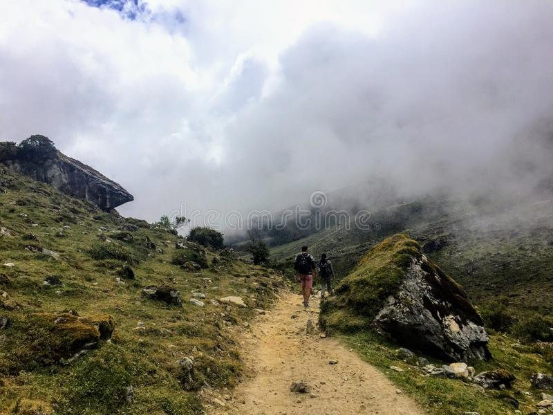 A young group of international hikers, led by their local Inca guide, navigate the Andes mountains through the clouds royalty free stock images