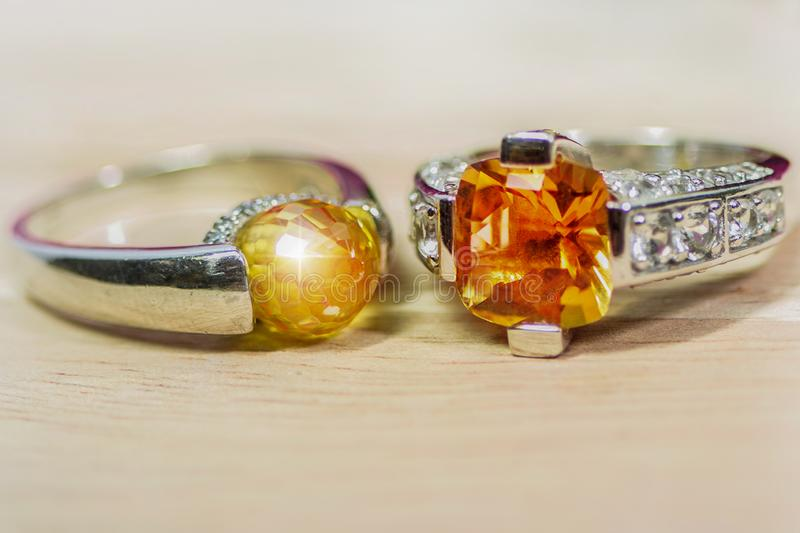 Cushion Cut Citrine Gemstone .yellow orange Round Cut and Diamond Ring.Placed on a beautiful light wood floor stock images