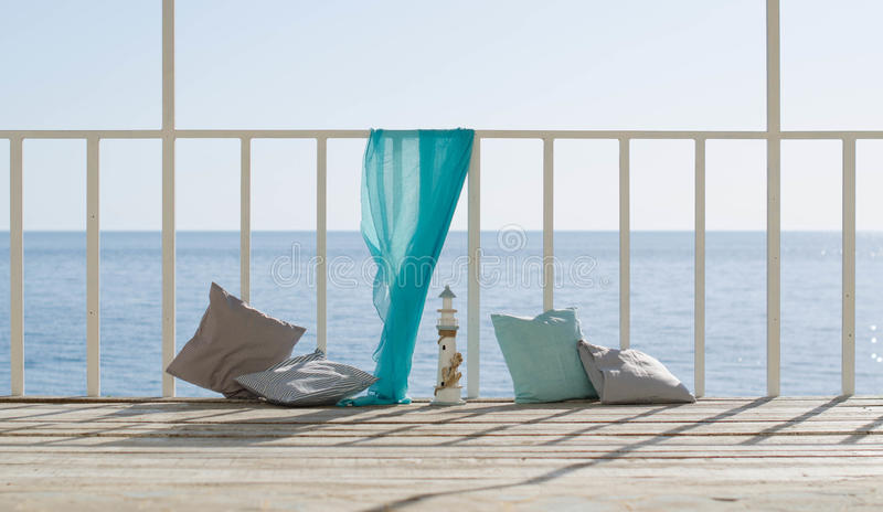 Cushions and a blue scarf on the background of the sea royalty free stock images