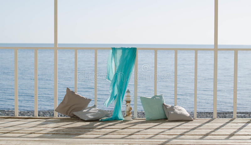 Cushions and a blue scarf on the background of the sea stock image