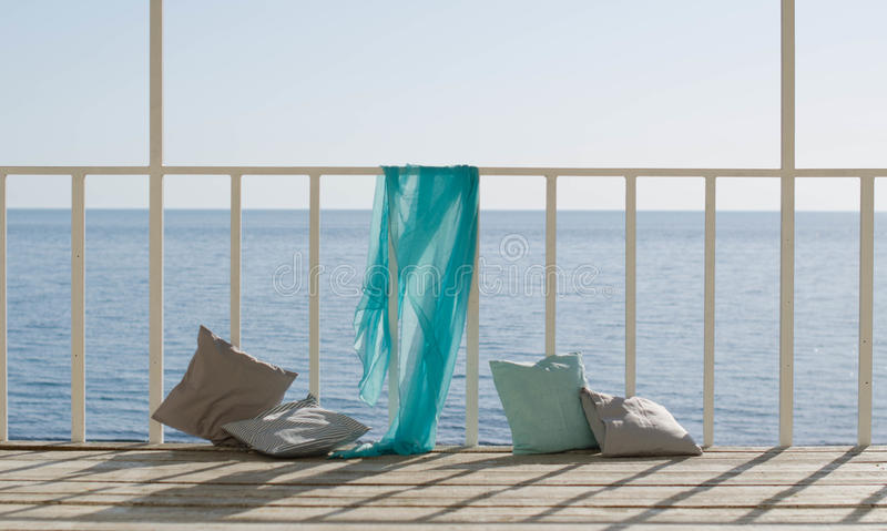 Cushions and a blue scarf on the background of the sea stock photography