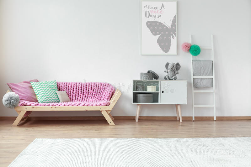 Cushions on a couch. Colorful cushions lying on a wooden pink couch in kid room with poster stock photography