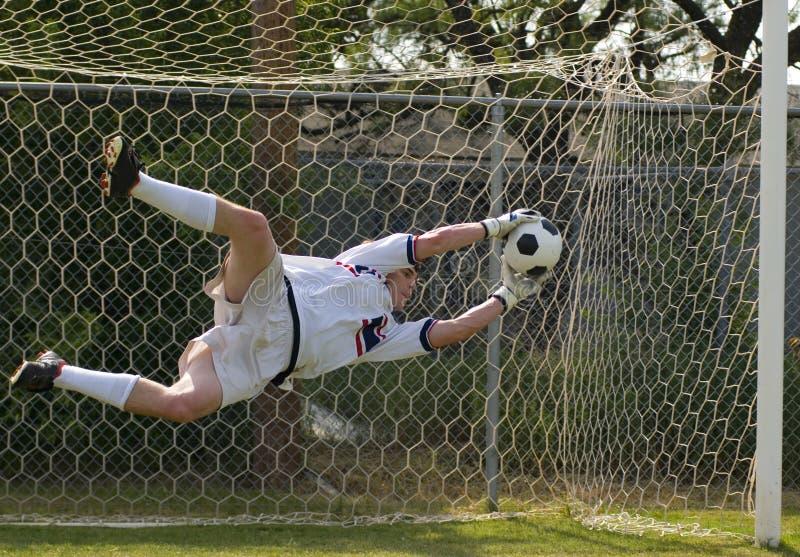 Custode di obiettivo di gioco del calcio di calcio che fa salvo immagine stock
