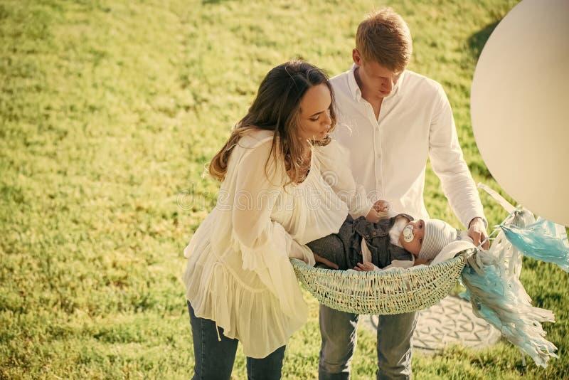 Custodia de los hijos Madre, hijo del bebé del control del padre en cesta en hierba verde imágenes de archivo libres de regalías