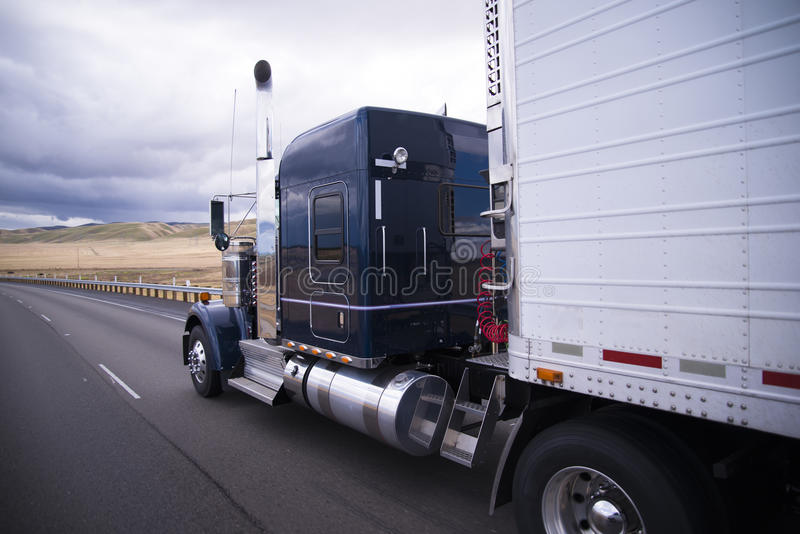 Custom big rig dark blue semi truck with reefer trailer. Classic bonneted American semi truck with chrome trim and a refrigerator trailer drive on the straight royalty free stock photos