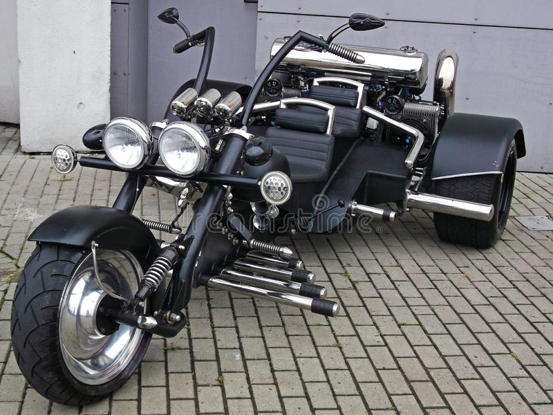 Custom black tricycle motorcycle. Powerful custom made black three wheeled motorcycle with a lot of chrome royalty free stock photos