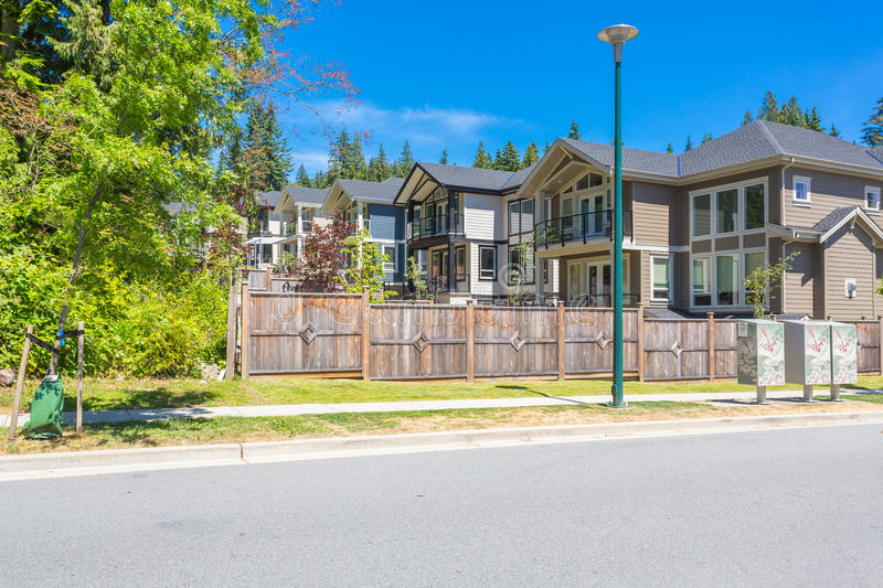 Custom built house. Row of townhouses. Custom built luxury house with nicely trimmed and designed front yard, lawn in a residential neighborhood, Canada royalty free stock photos