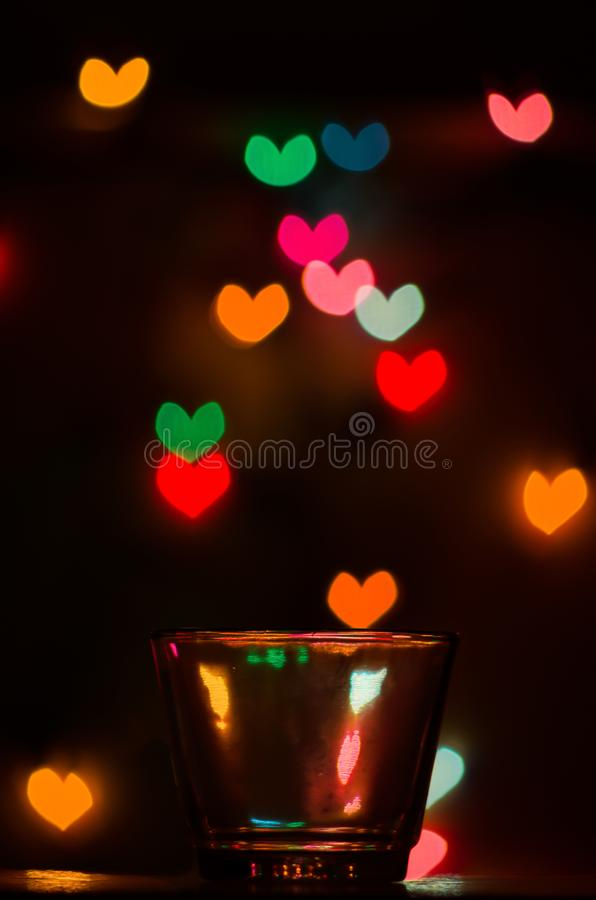 Custom heart shape bokeh behind a glass royalty free stock photography