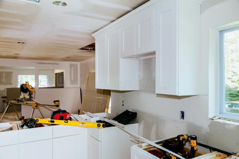 Custom kitchen cabinets in various stages of installation base for island in center. Installation of kitchen cabinets royalty free stock images