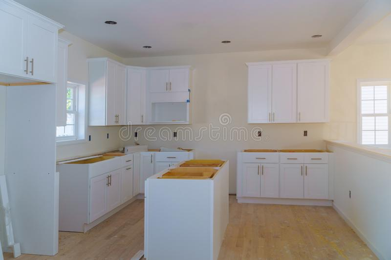 Custom kitchen cabinets in various stages of installation base for island in center. Installation of kitchen cabinets, installing, interior, house, home, work stock image
