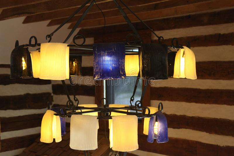 Custom log home with crafted blue and white chandelier lights. royalty free stock images