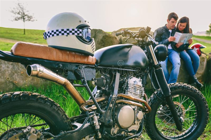Custom motorcycle with helmet and young couple looking at a map. Custom motorcycle with helmet and young couple sitting looking at a map. Selective focus on stock photography