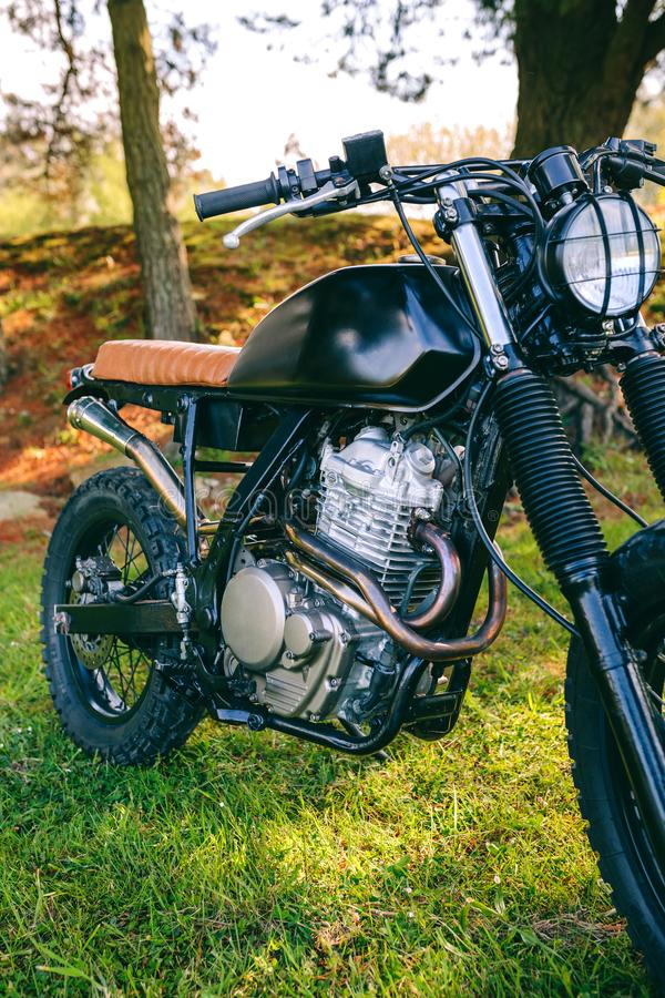 Custom motorcycle parked on the field. Closeup of beautiful vintage custom motorcycle parked on the field royalty free stock images