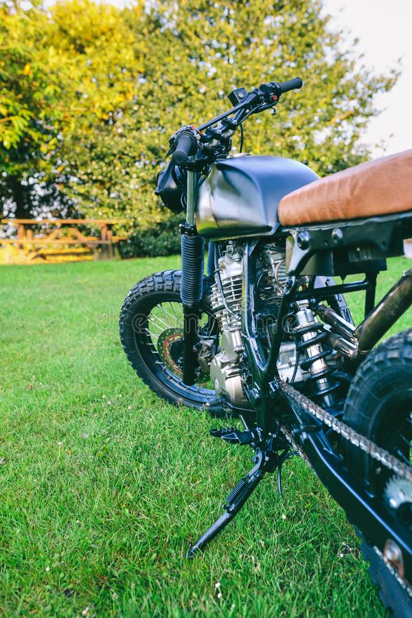 Custom motorcycle parked on the grass. Beautiful vintage custom motorcycle parked on the grass royalty free stock images