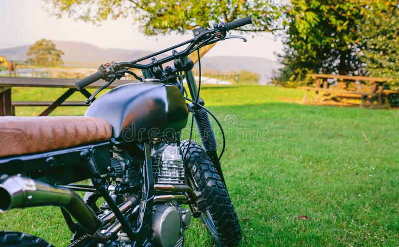 Custom motorcycle parked on the grass. Beautiful vintage custom motorcycle parked on the grass royalty free stock photography