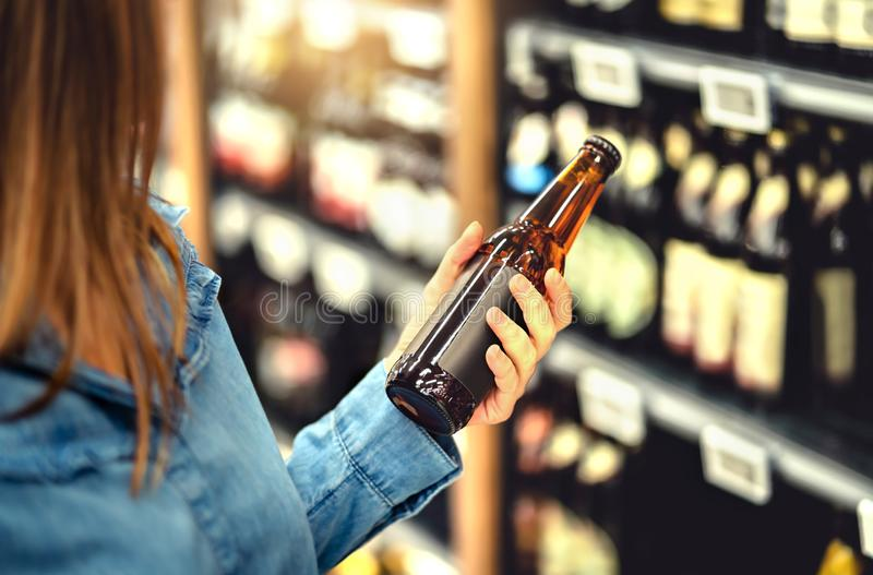 Customer buying beer in liquor store. Lager, craft or wheat beer. IPA or pale ale. Woman at alcohol shelf. Drink section and aisle in supermarket. Lady holding stock images