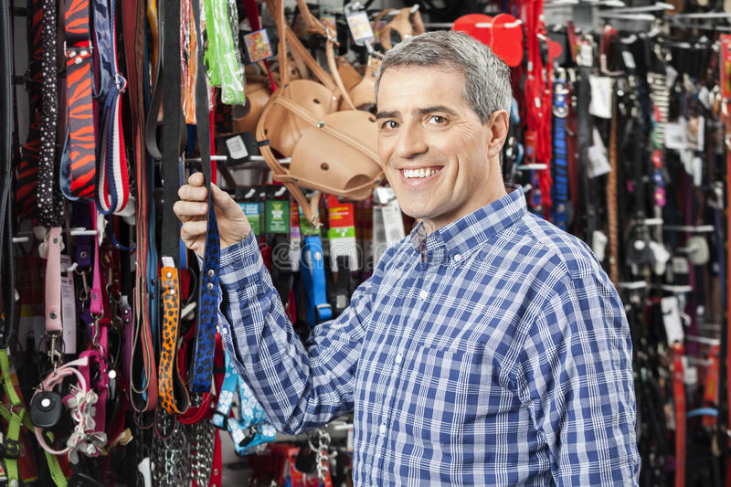 Customer Buying Pet Leash At Store. Portrait of happy male customer buying pet leash at store royalty free stock photography