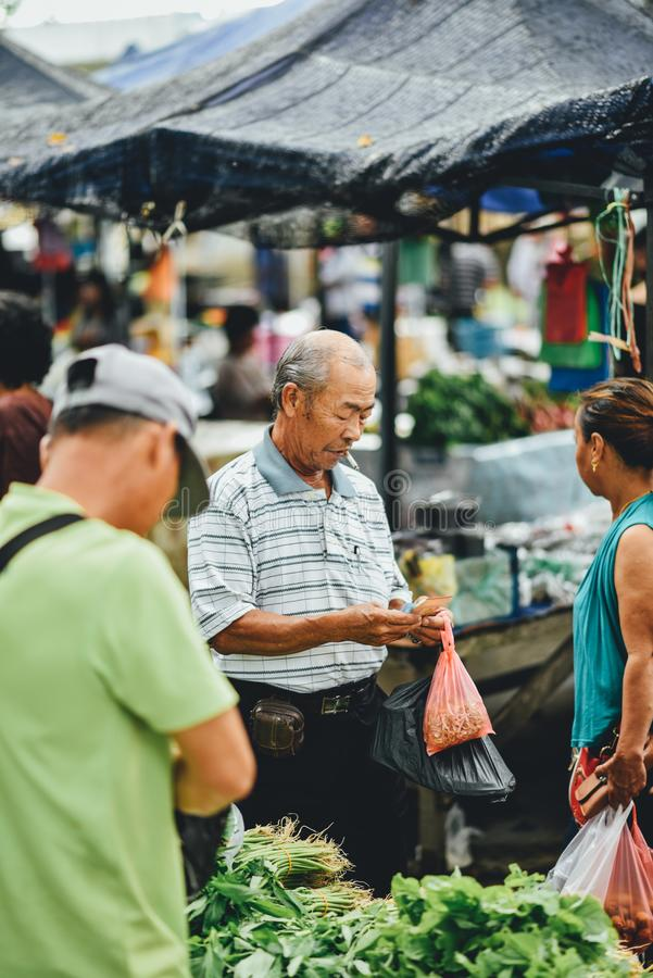 Customer buying vegetables at fresh market. A Chinese man buying some vegetables from a fresh market at Sri Aman town stock image