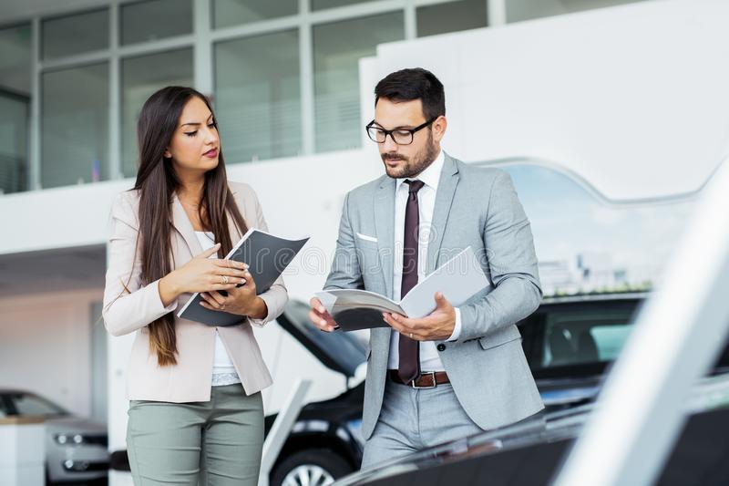 Professional salesperson selling cars at dealership to buyer royalty free stock photo