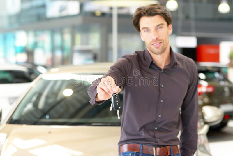 Customer in the car dealership holds the car key of the newly pu. Rchased car in his hand royalty free stock photo