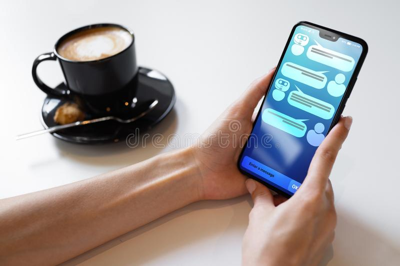 Customer and chatbot dialog on smartphone screen. AI. Artificial intelligence and service automation technology concept. Customer and chatbot dialog on stock photo