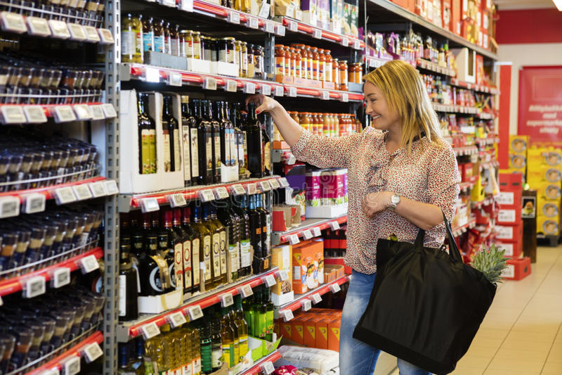 Customer Choosing Olive Oil In Supermarket royalty free stock photo