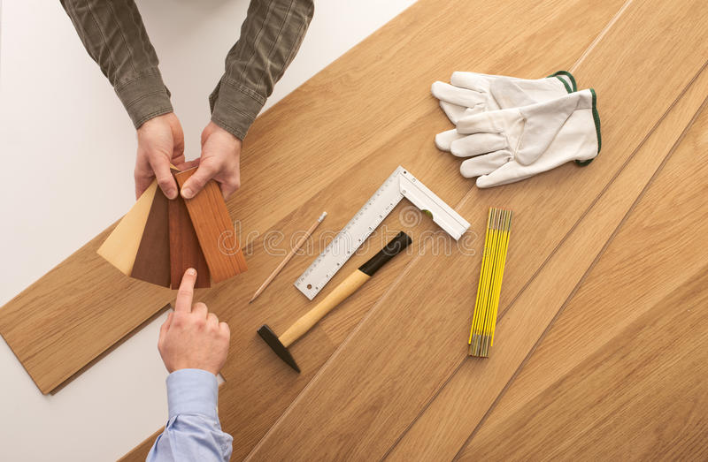 Customer choosing a wooden baseboard. Carpenter showing some wooden baseboard swatches to a customer and choosing a color, flooring installation and work tools royalty free stock photos