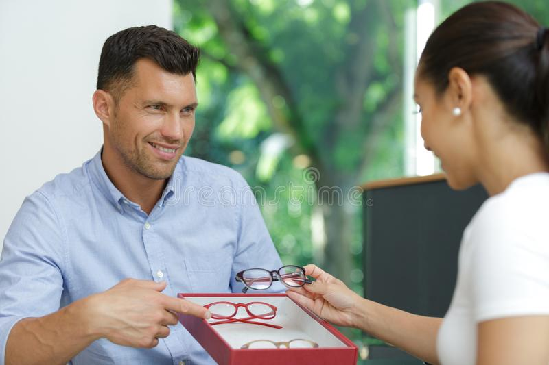 Customer considering selection eyeglasses to try. Customer considering a selection of eyeglasses to try stock photos