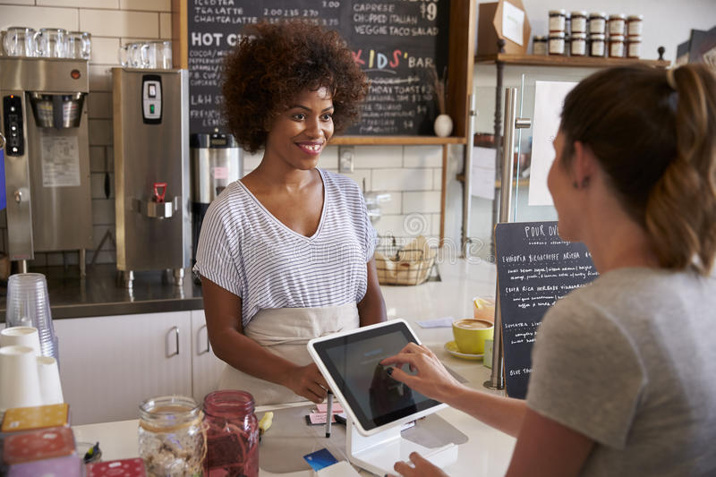 Customer at counter of coffee shop pays using touch screen stock image