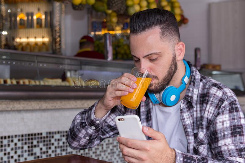 Customer drinking juice and reading articles and posts on his social media page outside of brazilian bakery. Concept of clientele. Handsome customer student man stock photos