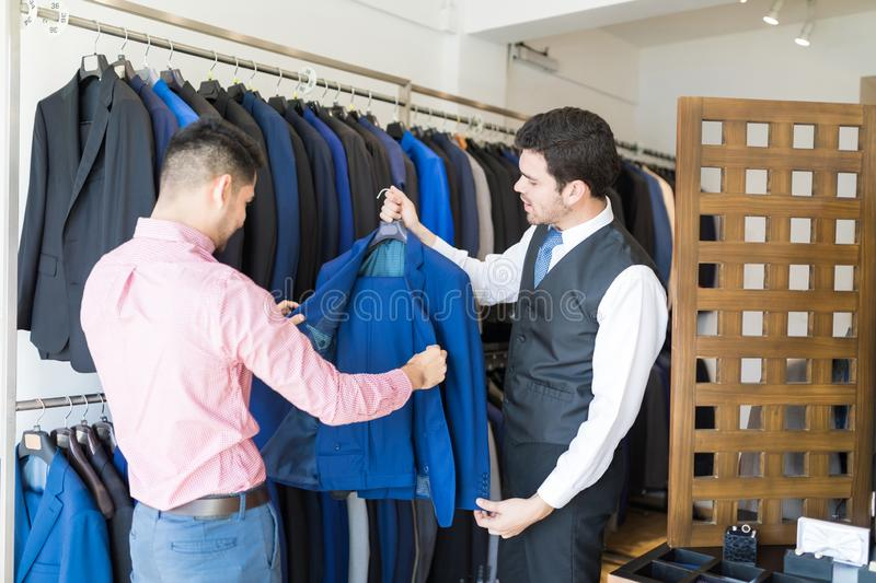 Customer Examining Blue Blazer In Rental Store. Young men checking suit before buying from clerk in shop stock photos