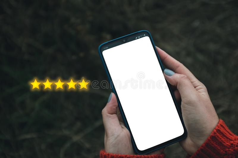 Customer Experience Concept. Digital phone user give five stars in his review and feedback stock photo