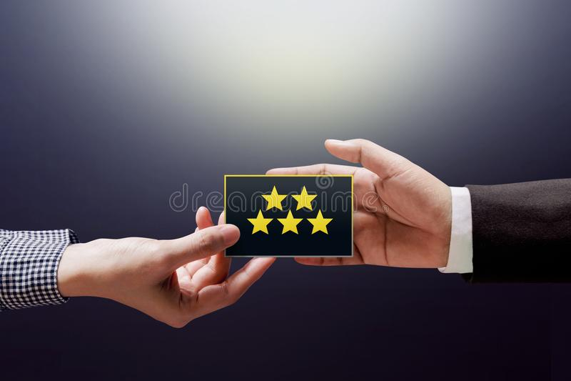 Customer Experience Concept, Happy Client Woman giving a Feedback with Five Star Rating on Card into a Hand of Businessman royalty free stock photo