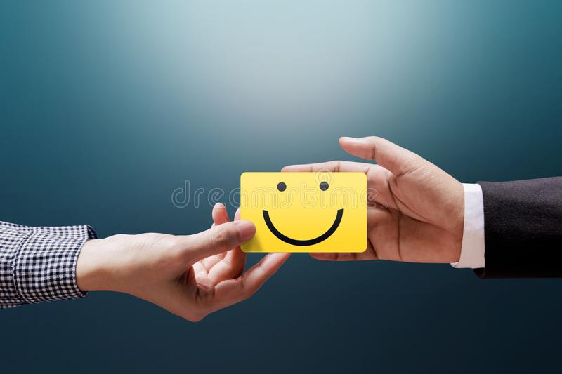 Customer Experience Concept, Happy Client Woman giving a Feedback with Happy Smiley Face Card into a Hand of Businessman stock photos