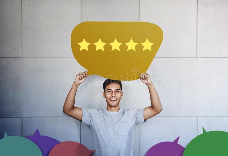 Customer Experience Concept. Young Man with Happy Face Showing Five Star Services Rating Satisfaction on Speech Bubble Card royalty free stock image