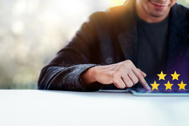 Customer Experiences Concept. a Modern Man Giving Five Stars Rating, Positive Review via Tablet. Client`s Satisfaction Surveys royalty free stock image