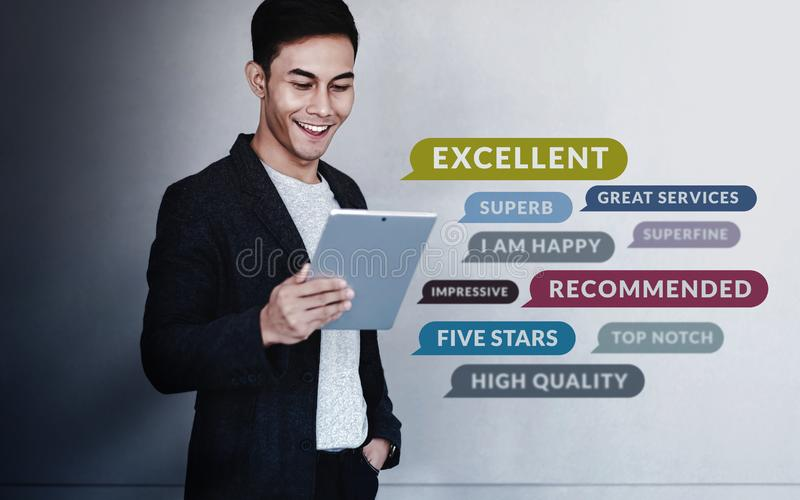 Customer Experiences Concept. a Young Happy Man Reading Positive Review Rating via Digital Tablet. Client`s Satisfaction Survey stock photo