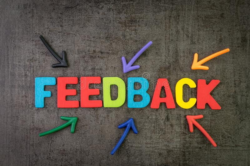 Customer feedback, review or rating concept, multi color arrows pointing to the word Feedback at the center of black cement. Chalkboard wall royalty free stock photo