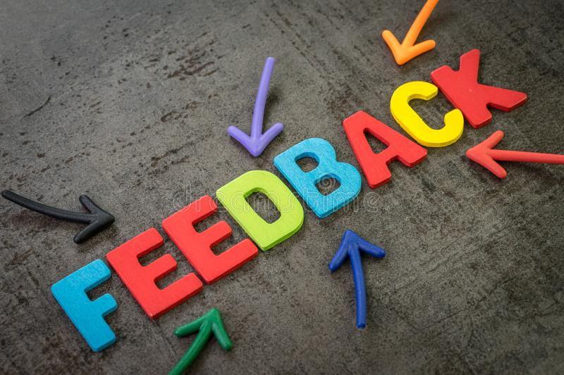 Customer feedback, review or rating concept, multi color arrows pointing to the word Feedback at the center of black cement. Chalkboard wall royalty free stock image