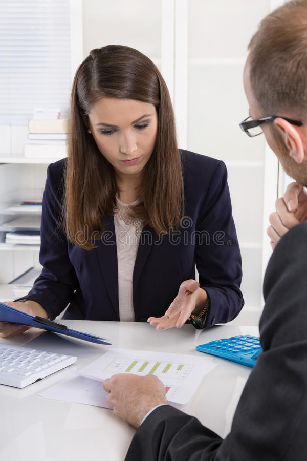 Customer and female financial agent in a discussion at desk. Customer and smiling female financial agent in a discussion at desk royalty free stock image