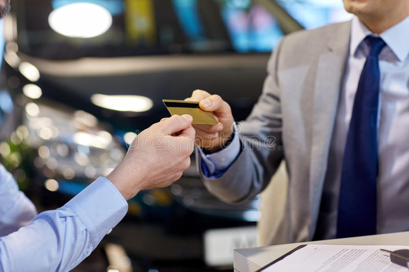 Customer giving credit card to car dealer in salon. Auto business, sale and people concept - close up of customer giving credit card to car dealer in auto show royalty free stock photo