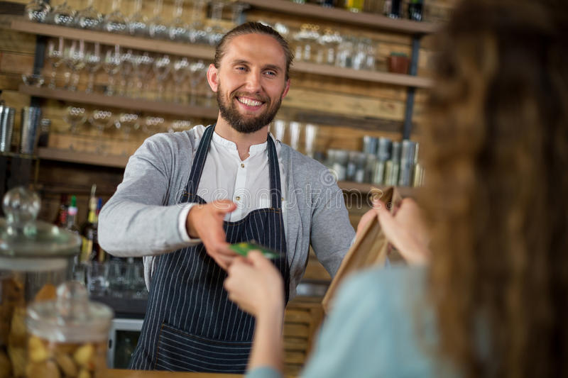 Customer giving credit card to waitress while receiving parcel at counter. In caf royalty free stock photos