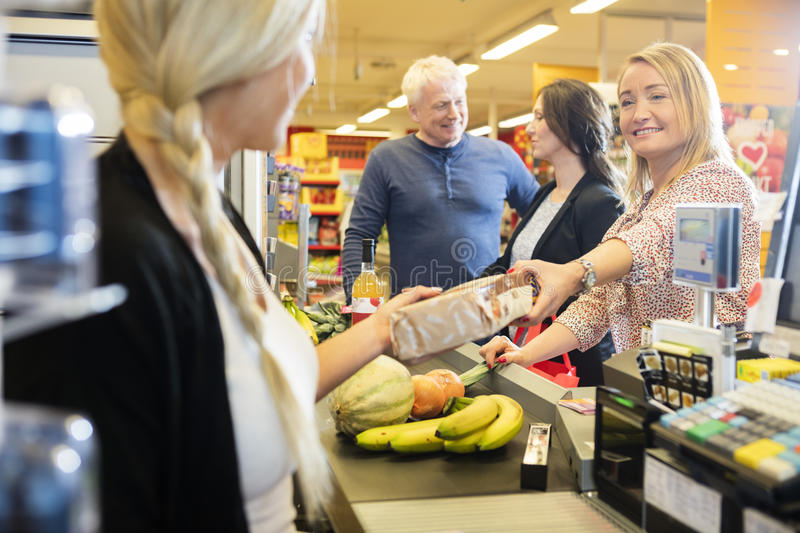 Customer Giving Packet To Cashier At Checkout Counter. Smiling female customer giving packet to cashier at checkout counter in supermarket royalty free stock photos